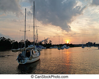 Sailboat at Sunset - A sailboat frames this sunset along the...