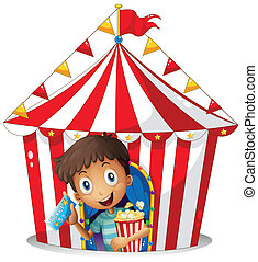A young boy with a ticket and a popcorn near the tent -...