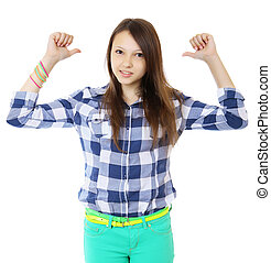 Young teen girl pointing behind with her thumb. Young woman...