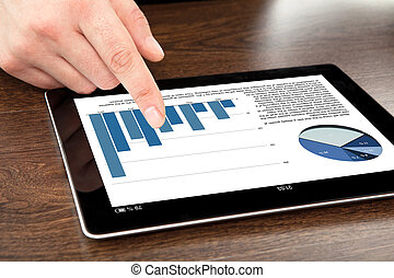 businessman points his finger at a computer tablet with graphics on a screen