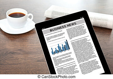 computer tablet with business news in a screen on a table at...