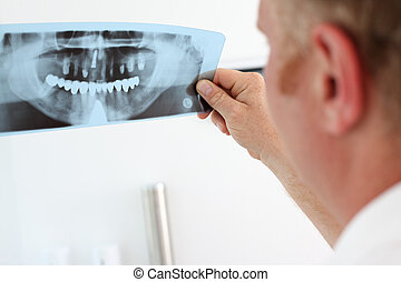 dentist looking at dental x-ray - Image of male doctor...