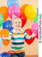 smiling child boy with balloons on birthday party