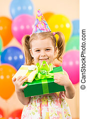 smiling child girl with gidts on birthday party