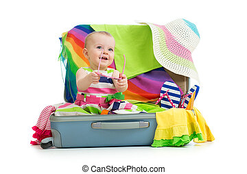 Baby girl sitting in suitcase with things for vacation...