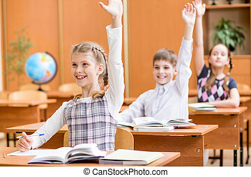 school children with raised hands at lesson in classroom