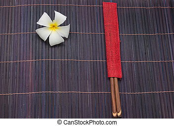 chopsticks and white frangipani plumeria flower on bamboo...