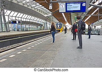 Travelers waiting for the train in Bijlmer station Amsterdam...