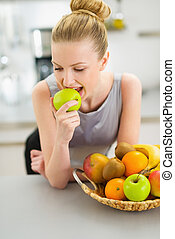 Happy young housewife eating apple in modern kitchen