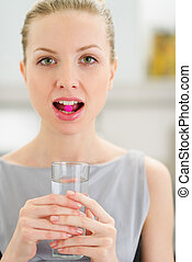 Young woman with pill in mouth