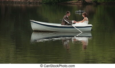 Bride and groom on rowboat - Boat with bride and groom...