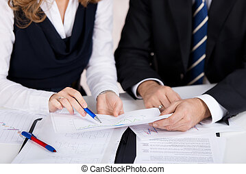 Businesspeople Communicating Over Linegraph At Desk