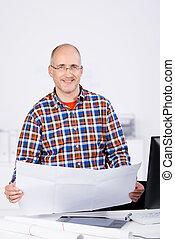 Confident Architect Holding Blueprint At Desk - Portrait of...