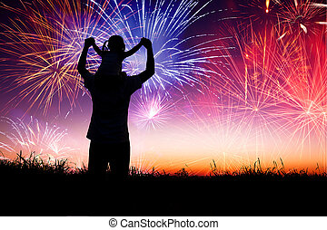 father with child standing on the hill and watching the fireworks