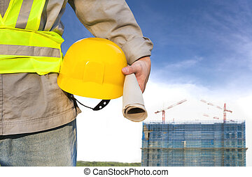 Construction building with worker holding hat