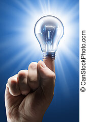 Idea - Mans hand with shining light bulb on blue