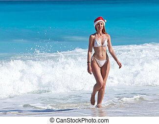 The young woman in a hat of Santa Claus goes on a beach at sea edge