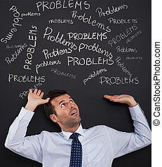 Businessman bending under stack of problems