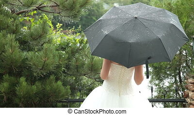Rainy Wedding Day - Bride sheltering from the rain under an...