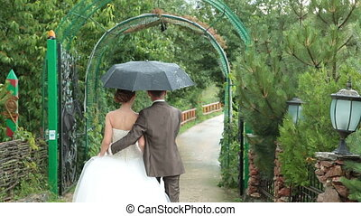 Wedding couple under an umbrella going away