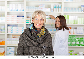 Senior with a scarf in the pharmacy with the pharmacist in...