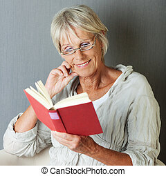 Senior Woman Reading Novel Against Grey Wall - Senior woman...