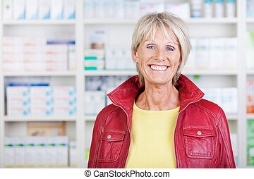Female Pharmacist Wearing Jacket While Smiling In Pharmacy -...