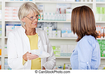 Pharmacist Giving Prescribed Medicine To Customer In...