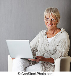 Senior Woman With Laptop Sitting On Couch Against Grey Wall...
