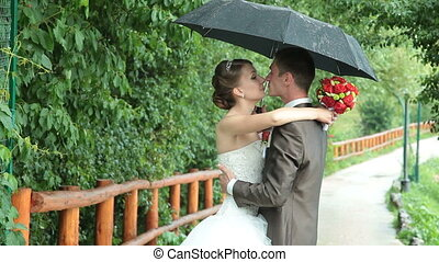 Bride and groom kissing under rain