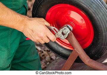 Repairing a wheelbarrow - Closeup of a man reparing red...