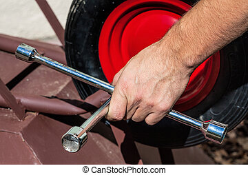 Wheel fixing with a spanner - Closeup of fixing wheelbarrows...