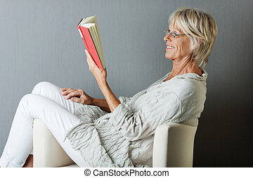 Happy senior woman reading a book sitting on sofa - Stylish...