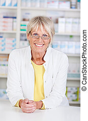 Portrait of a pharmacist in the pharmacy leaning on the desk
