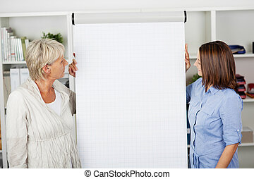 Two women looking at the flipchart in office