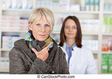 Unwell Senior Woman In Sweater With Pharmacist In Background...