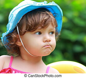 Angry baby girl looking in blue hat on summer background....