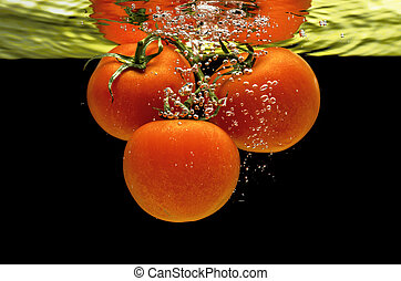 Fresh tomatoes dropped into water - A branch of fresh tomato...