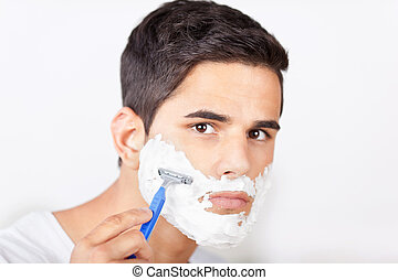 Young Man Shaving - Portrait of young man shaving