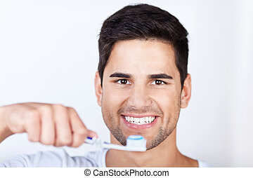 Young Man Brushing Teeth At Home - Closeup portrait of young...