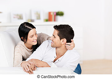 Loving couple cuddling on the sofa - Loving attractive young...