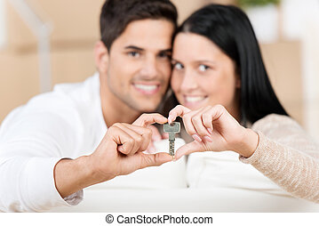 Happy young couple holding their new house key - Portrait of...