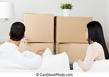 young couple between boxes - young couple between moving...