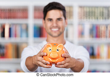 Smiling young man showing a piggy bank - Closeup of a...