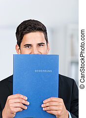 Male business executive holding a file