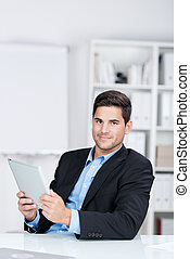 Confident Businessman Holding Digital Tablet At Desk