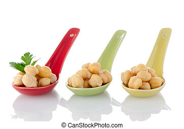 chickpeas over spoons - chickpeas over ceramic spoons on...