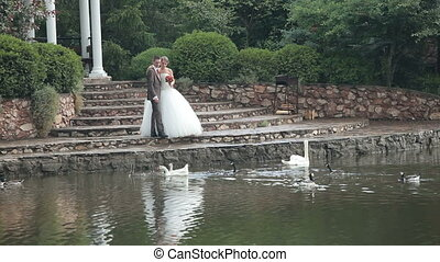 Bride and groom by the pond in the park