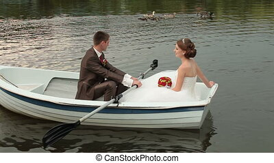 Wedding couple rowing boat on the pond