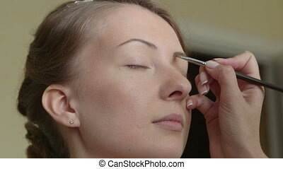 Young bride getting her makeup - Makeup artist helped the...